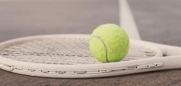 Raquete de tênis branca e bola verde na quadra, ativo, conceito de bem-estar