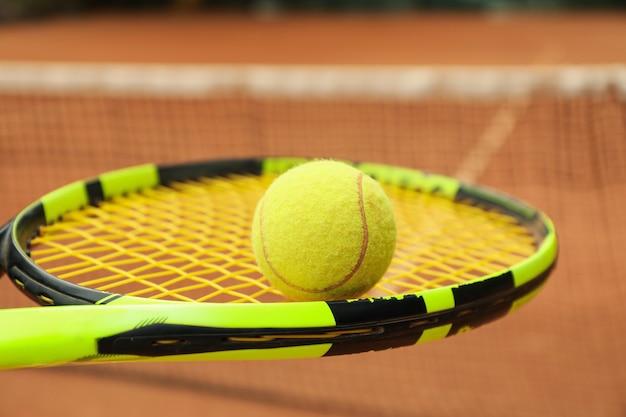 Raquete de tênis com bola de tênis contra quadra de saibro