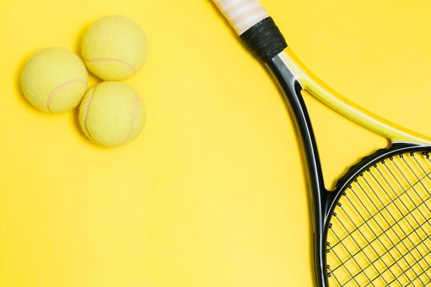 Raquete de tênis com bolas amarelas