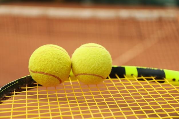 Raquete de tênis com bolas de tênis contra quadra de saibro