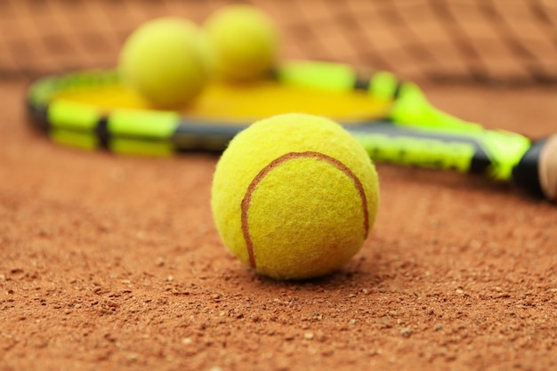 Raquete de tênis com bolas de tênis em quadra de saibro