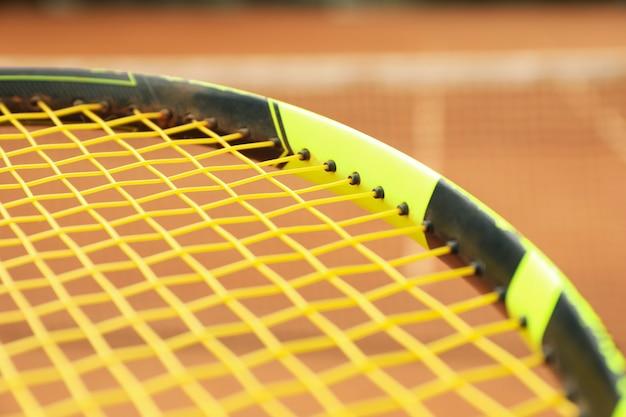 Raquete de tênis contra quadra de saibro, close-up