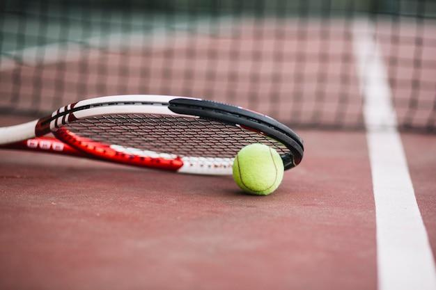 Raquete de tênis de baixo ângulo com bola ao lado