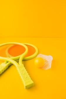 Raquete de tênis de plástico com bola e peteca contra pano de fundo amarelo