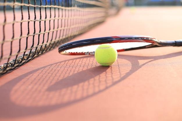 Raquete de tênis e a bola na quadra de tênis.