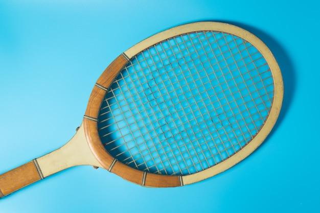 Raquete de tênis no fundo azul. equipamento esportivo.