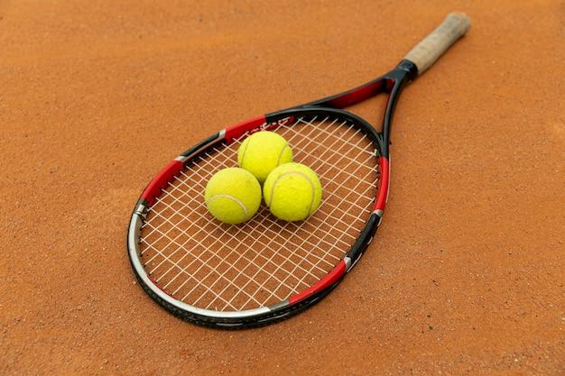 Raquete de vista alta e bolas de tênis na quadra