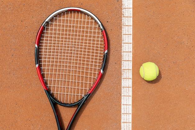 Raquete de vista superior e bola de tênis no chão do tribunal