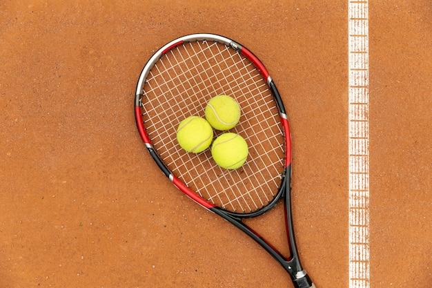 Raquete de vista superior e bolas de tênis no campo de tribunal