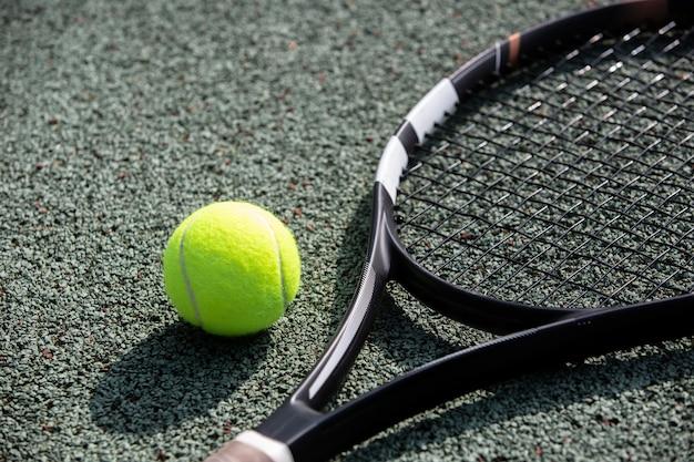 Raquete e bola de tênis na quadra de tênis profissional, conceito de esporte