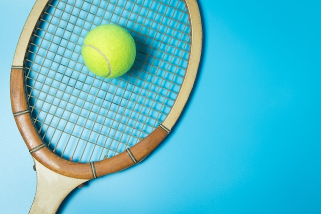Raquete e bola de tênis no fundo azul. equipamento esportivo. lay plana.