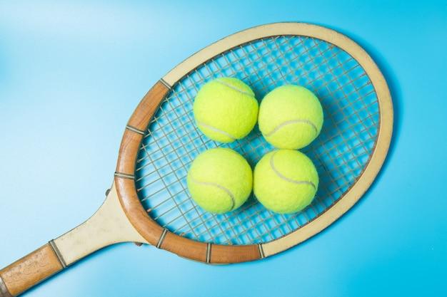 Raquete e bolas de tênis no fundo azul. equipamento esportivo.