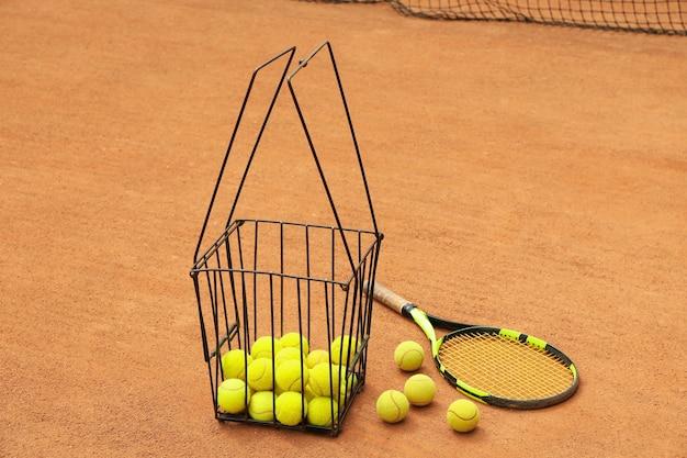 Raquete e cesto com bolas no saibro