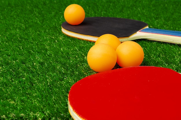 Raquetes de ping pong e bola na grama
