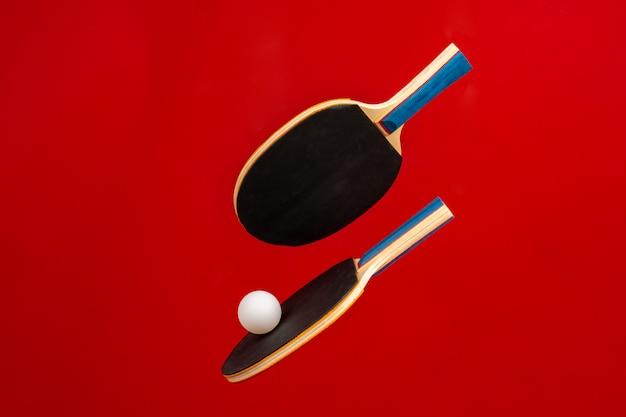 Raquetes de ping pong preto na superfície vermelha