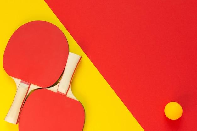 Raquetes de pingue-pongue vermelhas e bola laranja isoladas em um fundo vermelho e amarelo, equipamento esportivo para tênis de mesa