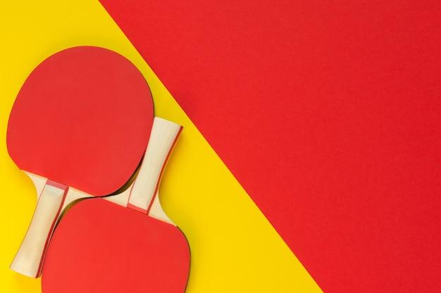 Raquetes de pingue-pongue vermelhas e isoladas em um fundo vermelho e amarelo, equipamento esportivo para tênis de mesa