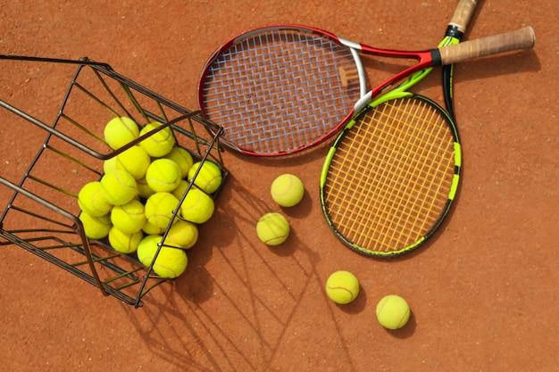 Raquetes de tênis com bolas de tênis em quadra de saibro