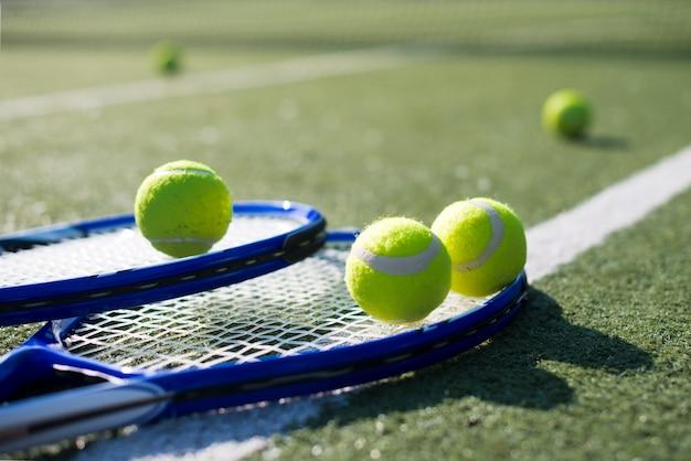 Raquetes de tênis de close-up e bolas no chão