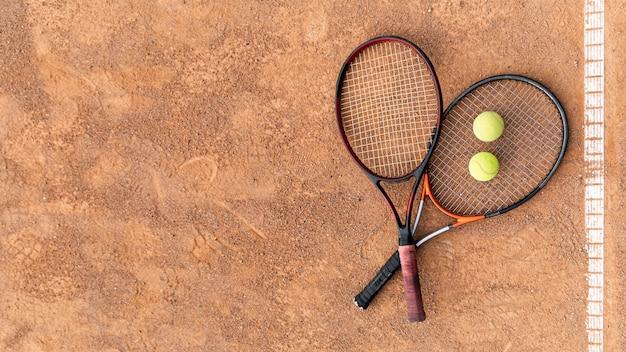 Raquetes de vista superior com bolas de tênis no chão