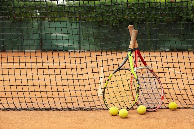 Raquetes e bolas de tênis contra rede em quadra de saibro