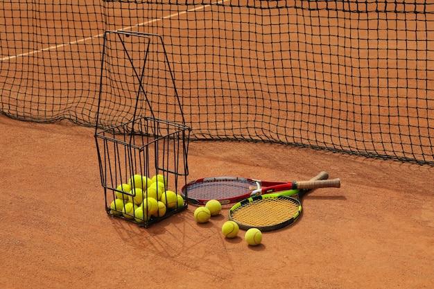 Raquetes e cesto com bolas de tênis em quadra de saibro