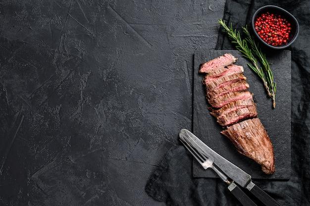Raro médio do bife de flanco cortado da carne. fundo preto. vista do topo. copyspace