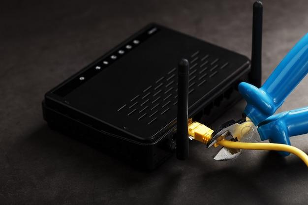 Rasgando e cortando com cortadores de fio azul a conexão de rede do fio amarelo da conexão com a internet.