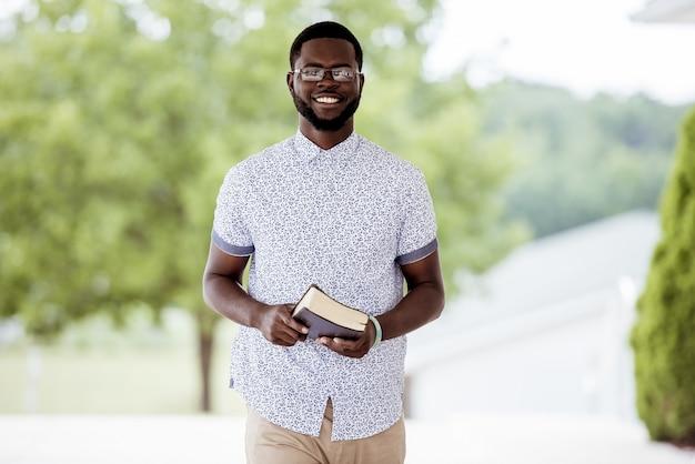 Raso foco tiro de um homem em pé, segurando a bíblia e olhando para a câmera