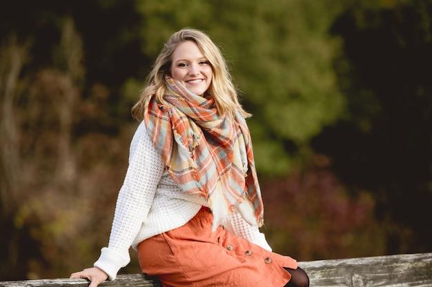 Raso foco tiro de uma mulher sentada em um de madeira e sorrindo para a câmera