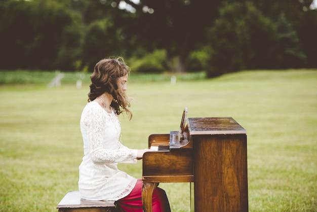 Raso foco tiro de uma mulher tocando piano