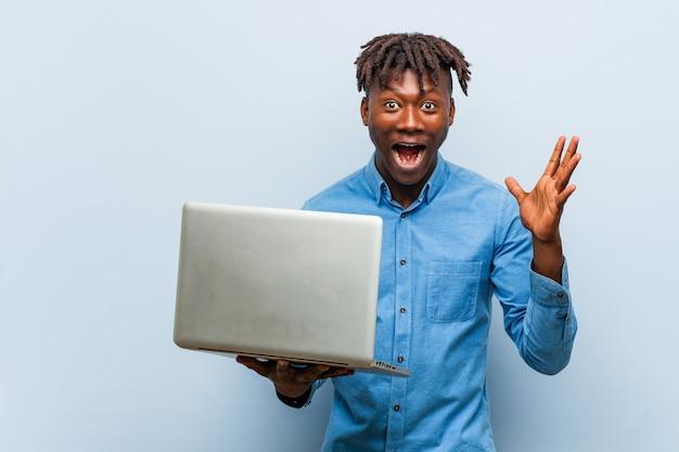 Rasta jovem negro segurando um laptop comemorando uma vitória ou sucesso