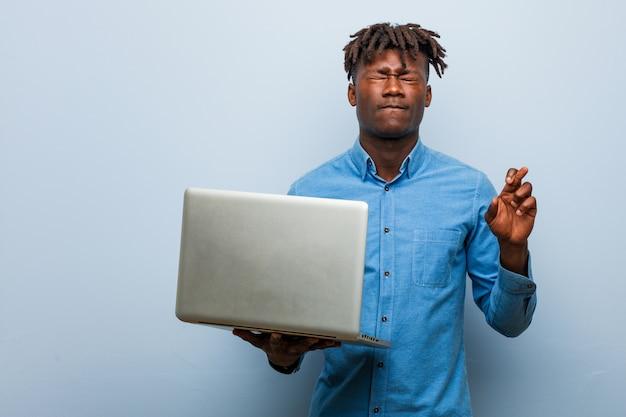 Rasta jovem negro segurando um laptop cruzando os dedos por ter sorte
