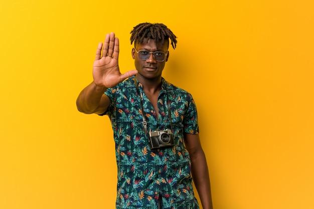 Rasta preto jovem vestindo um olhar de férias em pé com a mão estendida, mostrando o sinal de stop, impedindo-o.