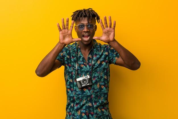 Rasta preto jovem vestindo um olhar de férias mostrando o número dez com as mãos.