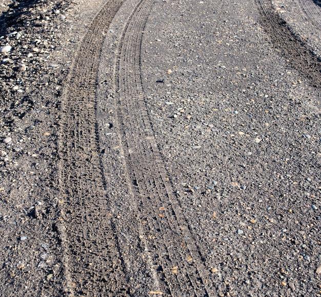 Rasto de pneu de carro em fundo de estrada suja