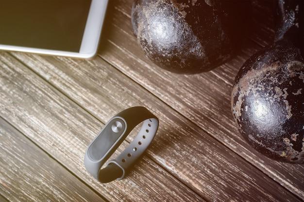 Rastreador de aptidão, smartphone e halteres em fundo de madeira