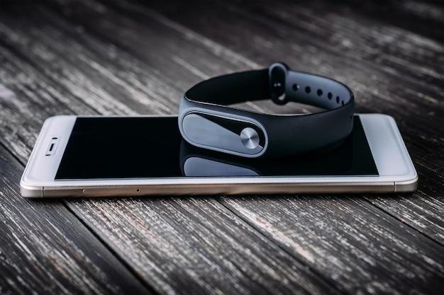 Rastreador de fitness preto no smartphone branco na mesa de madeira
