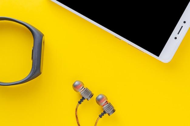 Rastreador de fitness, smartphone e fones de ouvido em um amarelo