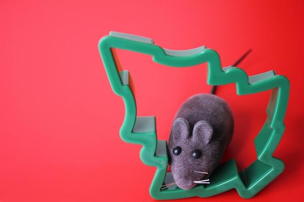 Rato de brinquedo e uma árvore de natal em um fundo vermelho