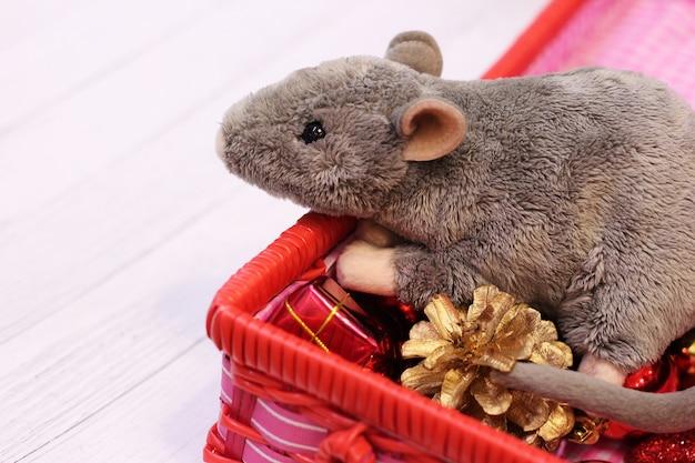 Rato de brinquedo macio cinza em uma caixa com brinquedos de natal