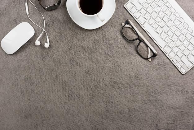Rato; teclado; xícara de café; fone de ouvido; relógio de pulso em fundo cinza