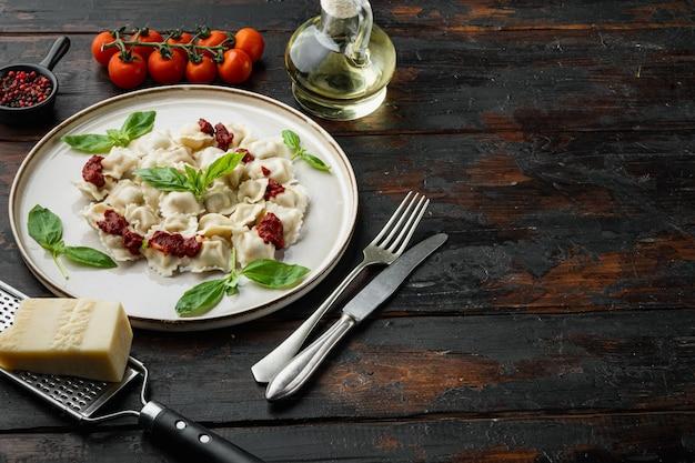 Ravioli apetitoso com molho de tomate, queijo e manjericão com parmesão de manjericão e tomate em prato branco sobre fundo de mesa de madeira escura velha, com copyspace e espaço para texto
