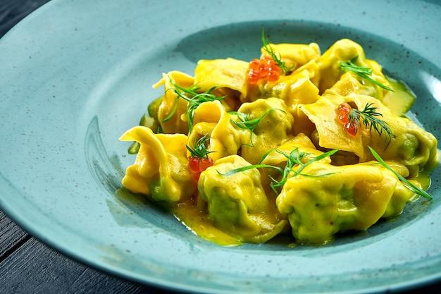 Ravioli caseiro de dar água na boca com salmão e caviar, servido com molho de pudim em prato azul sobre superfície de madeira escura. prato da cozinha italiana