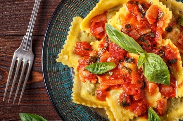 Ravioli com molho de tomate e manjericão no escuro