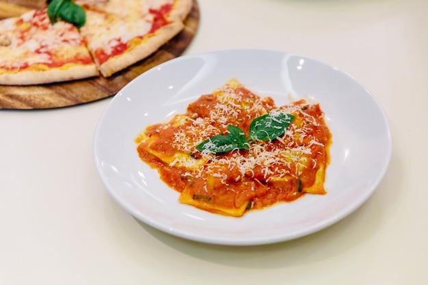Ravioli com molho de tomate e manjericão no topo com fatias de queijo parmesão