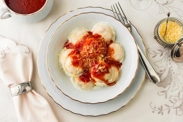 Ravioli com molhos de tomate e queijo ralado na tigela de cerâmica contra a toalha de mesa