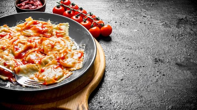 Ravioli com tomate cereja e molho. na superfície rústica preta