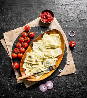 Ravioli com tomate, molho e rodelas de cebola. em preto rústico
