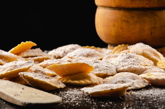 Ravioli cru saboroso com farinha e manjericão na mesa de madeira